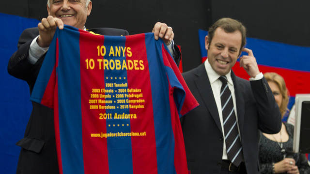 supporters club president holding a commemorative shirt before the futbol club barcelona president