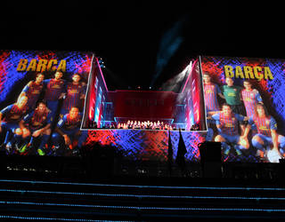 view of the masia building on the day of its inauguration with the images of the players projected onto the facade