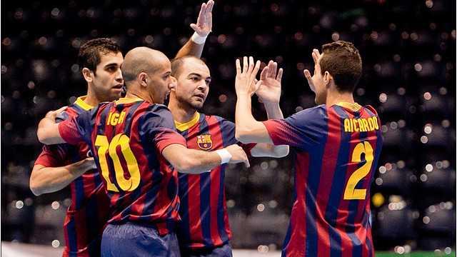 A circle of Barça players high-five to celebrate a goal in uefa elite round