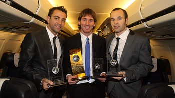 Xavi, Messi and Iniesta pose with their trophies in 2010 on the plane back