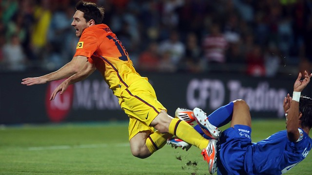 Leo Messi on the receiving end of a tackle at the Coliseum last season / PHOTO: MIGUEL RUIZ-FCB