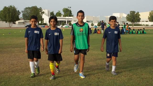 Quatre nens beneficiaris del projecte caminant a la càmera amb els uniformes del FutbolNet