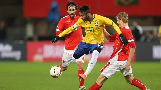 Neymar sedang mengiring bola dibayangi dua lawan