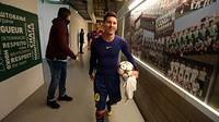 Messi, com a bola da partida, no túnel de vestiários do GSP Stadium.