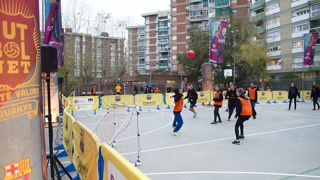 Un grup de joves juguen a futbol en el camp esportiu d'una escola
