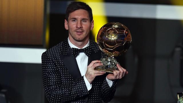 Messi sedang mengangkat Ballon d'Or nya yang keempat
