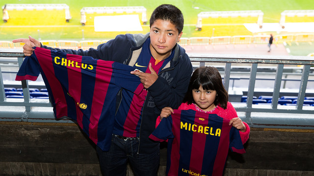 El jove Carlos i la seva germana petita Micaela sostenen unes samarretes del barça amb els seus noms estampats