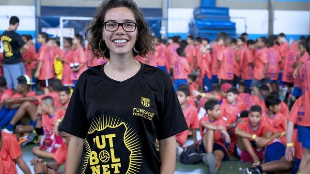 L'educadora Laia Martín amb una samarreta on hi posa 'FutbolNet' envoltada dels nens que apliquen el projecte