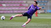 Xavi sedang menendang bola di lapangan