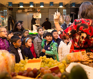 Un grupo de alumnos de primaria atienden a la profesoara durante una de las visitas en el Mercado de la Concepció