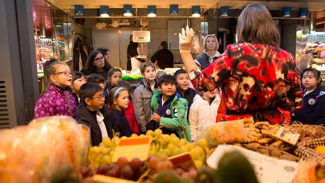 Un grup d'alumnes de primària atén les explicacions d'una de les professores.