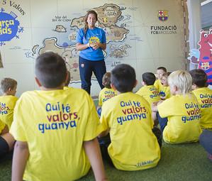 Una monitora explica a los niños el contenido del proyecto en una de las salas del Club