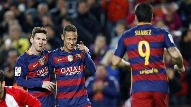 Messi e Neymar abraçados, esperam Suárez que vem correndo para celebrar um gol.
